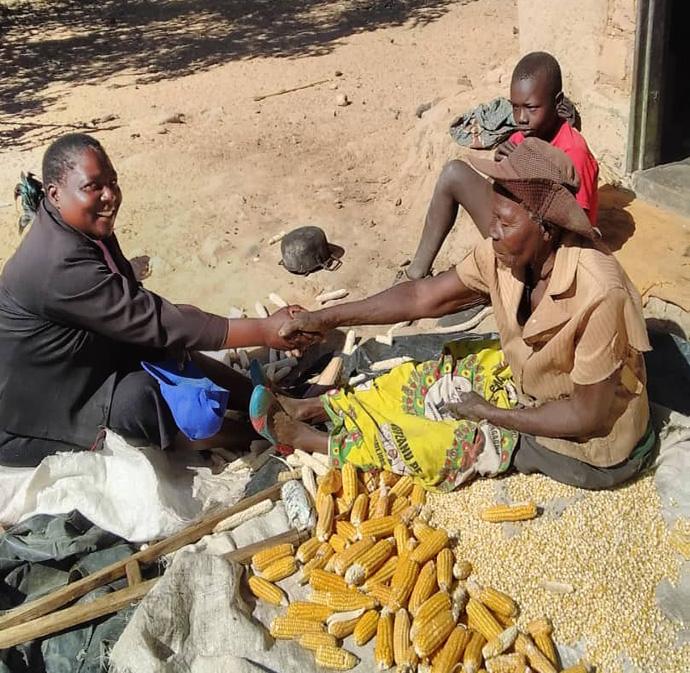 The Rev. Annamore Kahlari (left) visits with church members Mbuya Marble (front) and Danmore Chagonyera while they prepare corn for storage at their home in the Chitsiwa Circuit near Makoni Buhera, Zimbabwe. Photo by Chenayi Kumuterera, UM News.