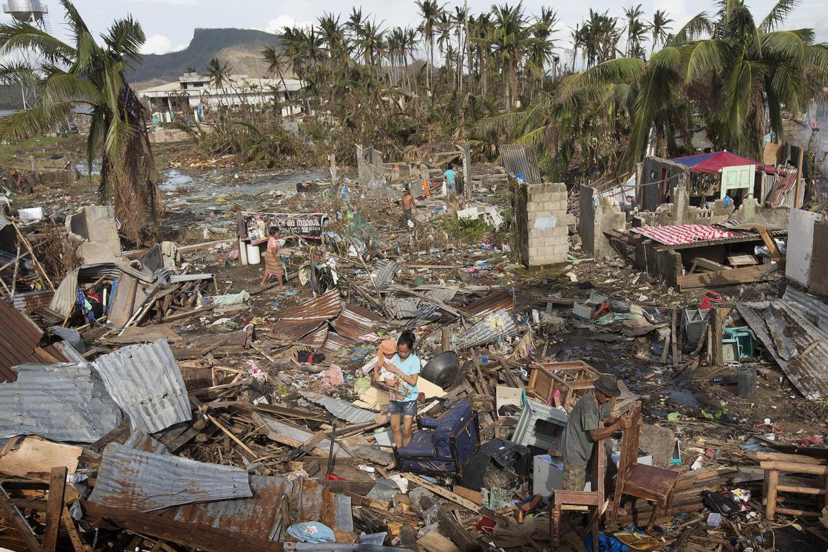2013년 필리핀 타클로반 지역의 이재민들이 태풍 하이옌이 휩쓸고 지나간 후 쌓인 잔해들 사이에서 쓸만한 물건들을 찾고 있다. 전 세계의 젊은 감리교인들이 지구 온난화에 맞서 싸우기 위해 함께 사역하고 있으며, 기후 변화의 최전선에 있는 취약한 지역 사회를 돕기 위해 노력하고 있다. 사진, 마이크 두보스, 연합감리교뉴스.