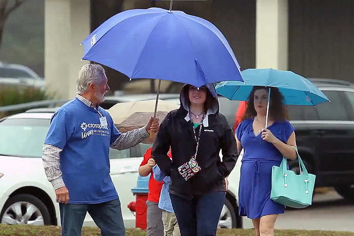 A volunteer holds an umbrella for a woman at Crosspoint, a United Methodist church in Niceville, Fla. Ninety percent of the congregation at its South Crestview campus volunteers in some capacity. Video image courtesy of Crosspoint via Vimeo by UM News.