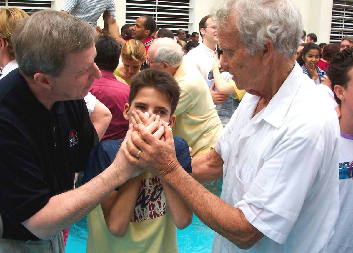 The Revs. H. Eddie Fox (right) and George Freeman join 50 other Wesleyan/Methodist clergy and bishops from throughout the Americas at a mass baptism of more than 200 adults and children in Havana in 2004. File photo by Roy Corbin.