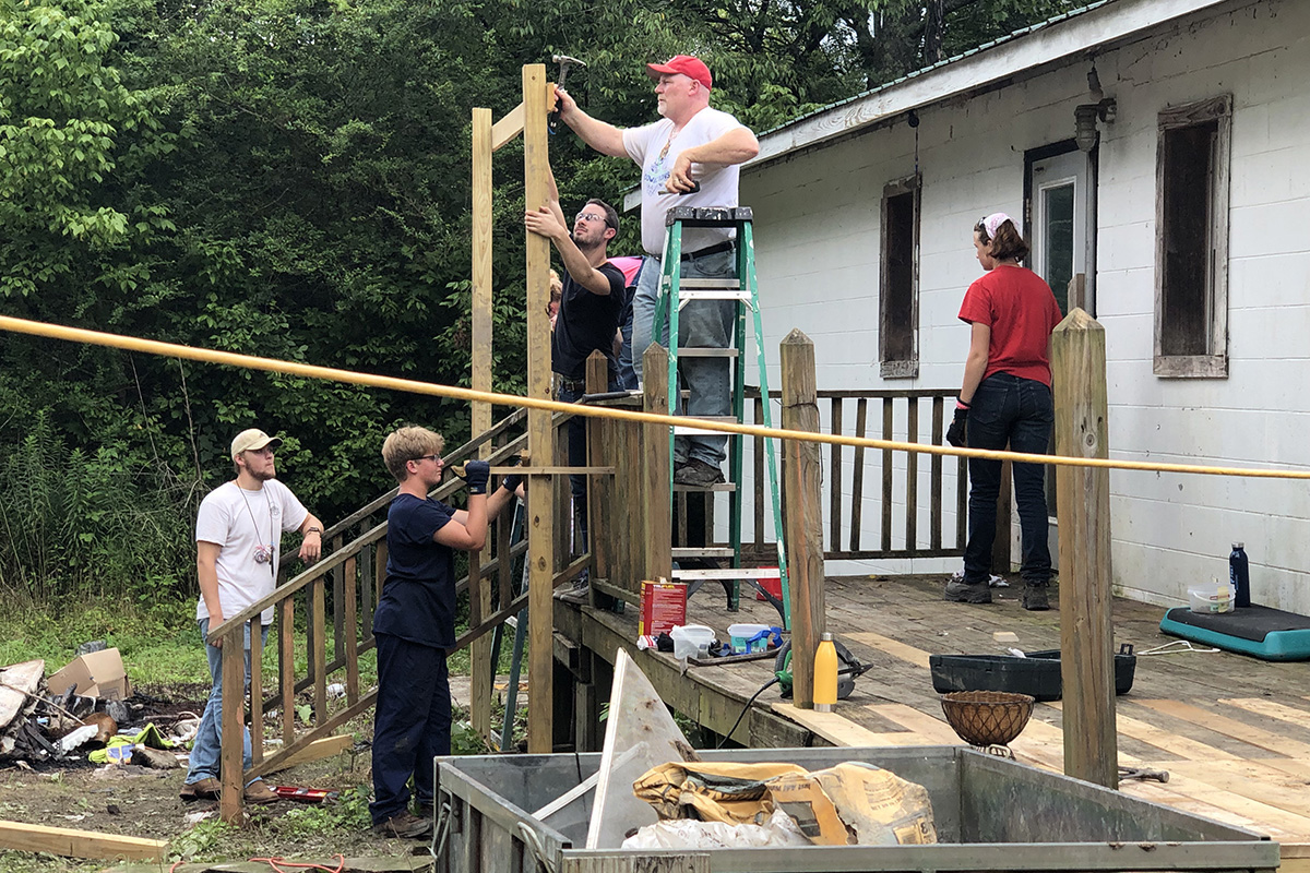 Youth and adults from Oregon United Methodist Church and St. Mary's Catholic Church, both in Oregon, Ill., repair the porch on a home in Tracy City, Tenn. The team volunteered with Mountain T.O.P., a ministry that serves families in the Cumberland Mountain region of southeast Tennessee. Photo by the Rev. Thomas Kim, UM News.