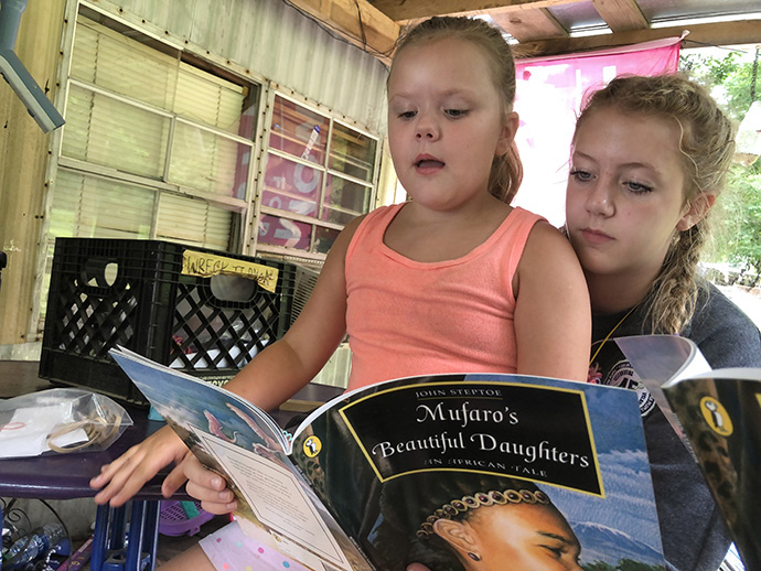 Nora Hammer (right) from St. Mary's Catholic Church in Oregon, Ill., reads with Lillian Clark, 8, at a volunteer worksite in Gruetli-Laager, Tenn. Photo by the Rev. Thomas Kim, UM News.