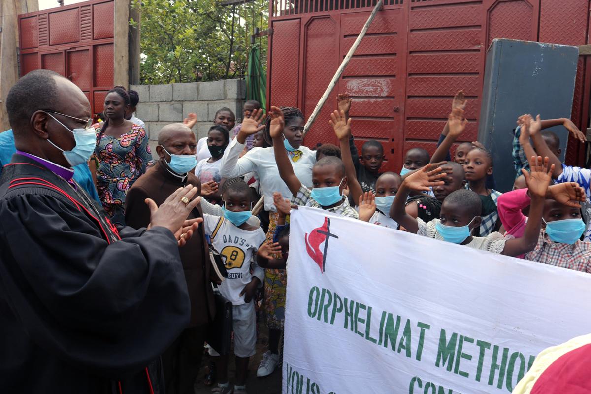 지난 5월 22일 발생한 니라공고 화산 폭발로 부모를 잃고 고아가 된 어린이들의 어려움을 살펴보기 위해 그들이 머무는 콩고 고마의 연합감리교회에 방문한 가브리엘 옘바 운다 감독(왼쪽 끝)이 아이들의 환영을 받고 있다. 콩고 연합감리교회는 40여 명의 아이들을 돌보고 있다. 사진 제공, 필립페 키투카 로롱가, 연합감리교뉴스.