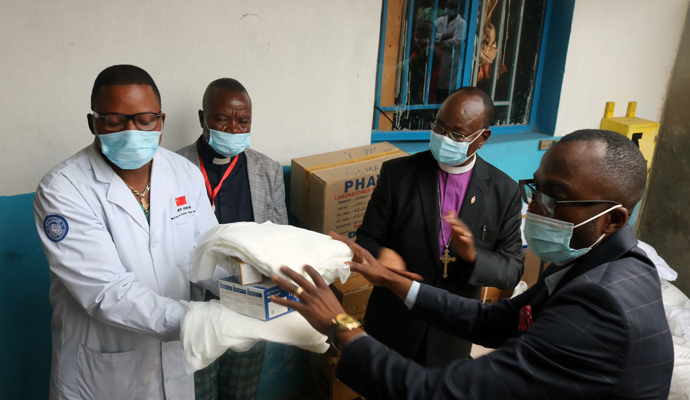 Bishop Gabriel Yemba Unda (center, in purple clerical shirt) delivers a batch of drugs to the Majengo United Methodist Health Center in Goma, Congo. A $10,000 grant from United Methodist Global Ministries' Global Health unit provided bed nets, medicine and medical supplies, personal protective equipment and hygiene kits. Photo by Philippe Kituka Lolonga, UM News.