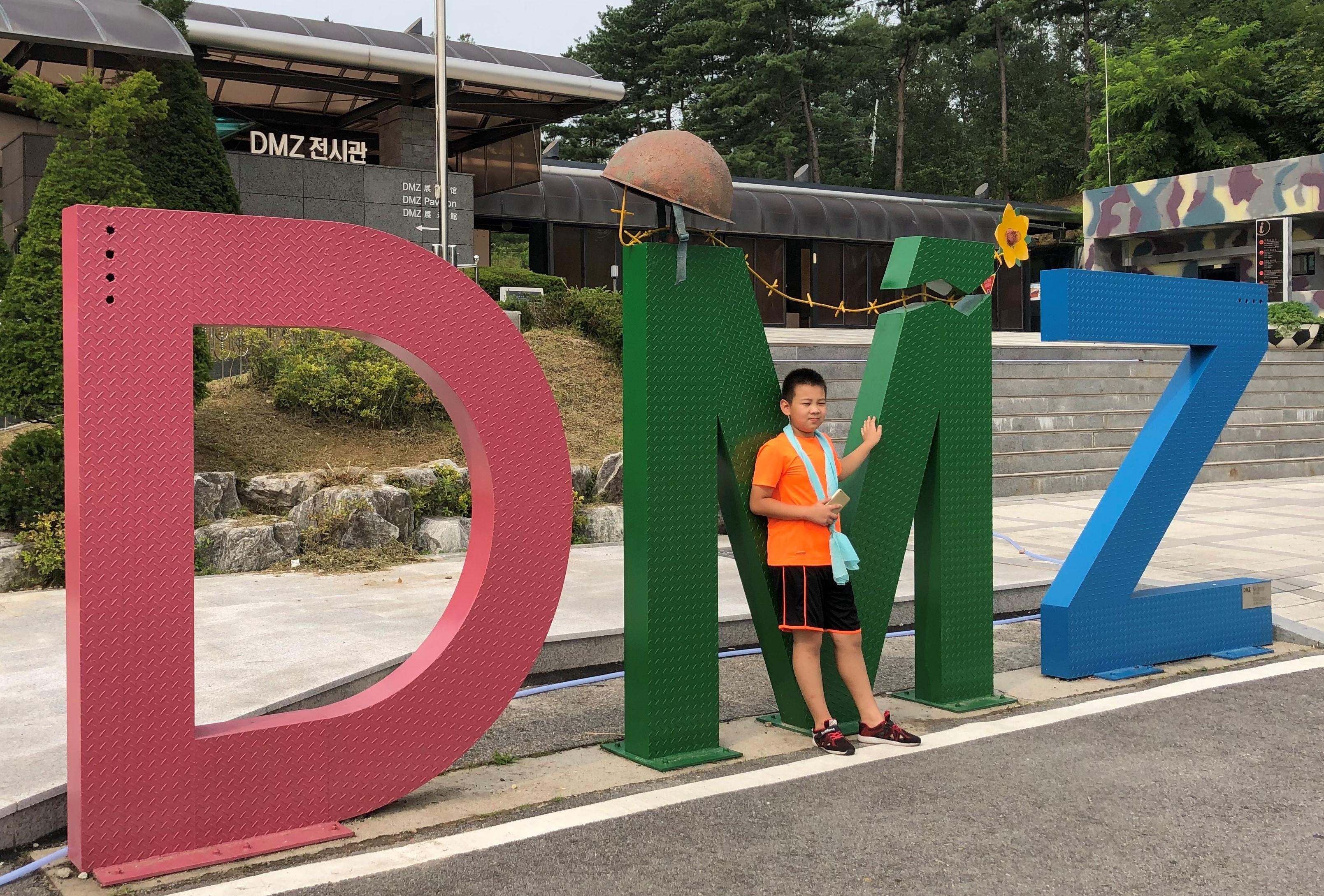 한 관광객 어린이가 DMZ (군사분계선, Military Demarcation Line) 전시관 앞에서 사진을 찍고 있다. 가운데 M자 위에 놓인 녹슨 철모와 꽃이 인상적이다. 사진, 김응선 목사, 연합감리교뉴스.