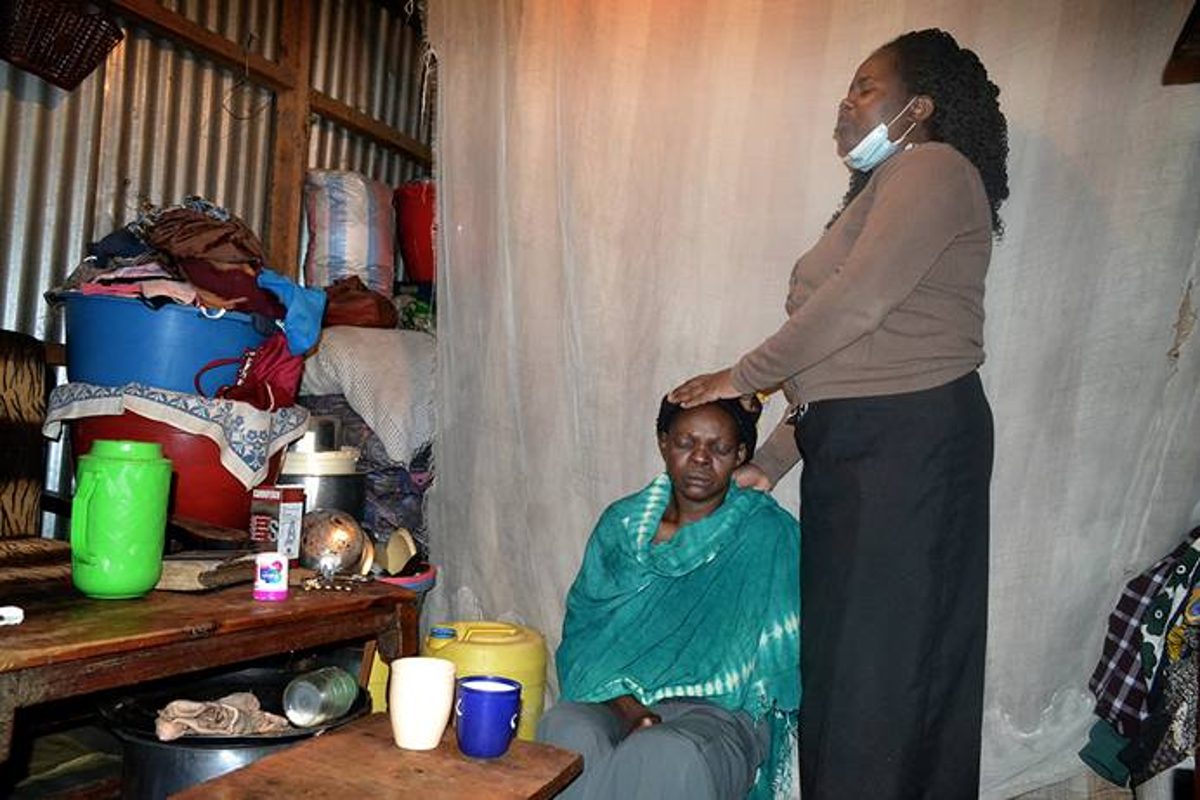 Roselyne Oyosa, a pastor at Huruma United Methodist Church in Nairobi, Kenya, prays for Agnes Nekesa at her house in the Huruma slums in Nairobi. Nekesa is battling breast cancer. Photo by Gad Maiga, UM News.