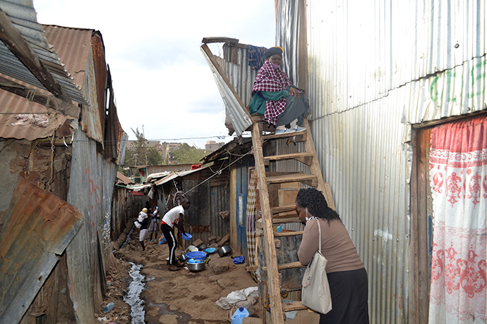 Pastor Roselyne Oyosa (front) visits with Agnes Nekesa at her home in the Huruma slums in Nairobi, Kenya. Nekesa, who has breast cancer, has to navigate several unstable wooden staircases to access her house. Photo by Gad Maiga, UM News.