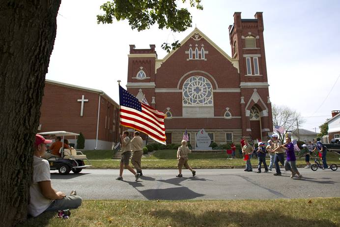 Boy Scouts parade in front of Leipsic (Ohio) United Methodist Church during the town's Fall Festival in 2010. As the Boy Scouts of America's sex abuse-triggered bankruptcy proceeds, United Methodist congregations are hearing from denomination leaders to hold off on renewing chartering relationships with Boy Scout troops. File photo by Mike DuBose, UM News.