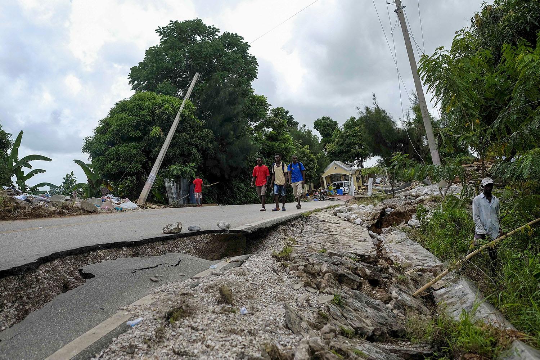 Moradores caminham em uma estrada danificada em Rampe, Haiti, na quarta-feira, 18 de agosto de 2021, quatro dias depois que um terremoto de magnitude 7,2 atingiu a parte sudoeste do país. Foto cedida por Associated Press / Matias Delacroix.