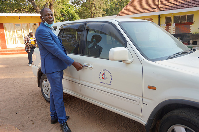 The Rev. Godknows Risinamhodzi, Chitungwiza Marondera District superintendent, unlocks a new vehicle that will be given to Learnmore Rungwandi, pastor in charge of the Hwedza United Methodist Circuit near Wedza, Zimbabwe. Rungwandi had been walking long distances to minister to her four local churches spread over a 37-mile radius. Photo by Kudzai Chingwe, UM News.