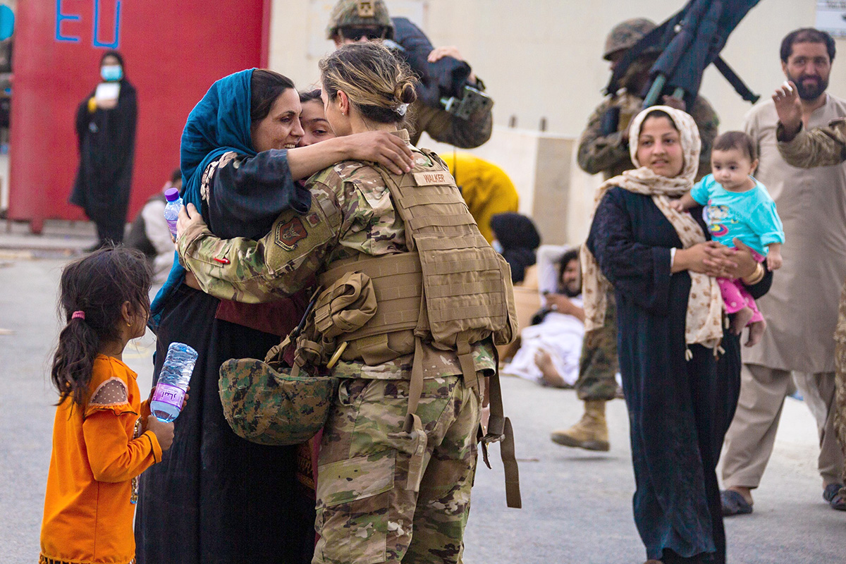 A U.S. airman with the Joint Task Force-Crisis Response embraces a mother after helping reunite her family at Hamid Karzai International Airport in Kabul, Afghanistan, Aug. 20. United Methodist churches, conferences, agencies and partner nonprofits are working to help arriving refugees make a good start in the U.S. Photo by Cpl. Davis Harris, U.S. Marine Corps.