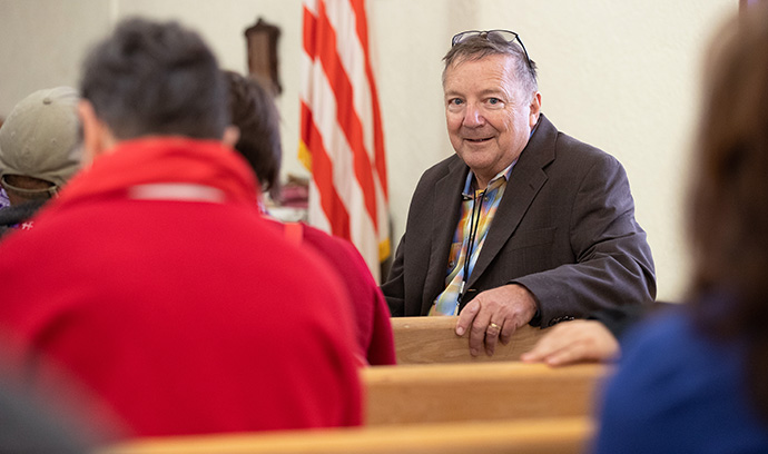 The Rev. George Miller briefs members of the United Methodist Immigration Task Force on a transitional shelter for immigrants at El Calvario United Methodist Church in Las Cruces, N.M., in 2019, when the church was preparing to host migrants who had crossed into the U.S. from Mexico. The church is now collecting supplies for Afghans whose first stop is a nearby U.S. military base. File photo by Mike DuBose, UM News.