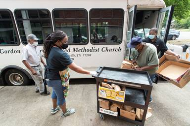 The Rev. Paula Smith (second from left) steadies a cart while volunteers Tim Morgan (in green T-shirt) and Richard Wilson load box lunches for distribution at Gordon Memorial United Methodist Church in Nashville, Tenn. A new study by Gammon Theological Seminary explores the pandemic's impact on Black United Methodist churches and leaders. File photo by Mike DuBose, UM News.