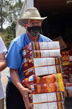 Texas Conference Bishop Scott Jones carries boxes of Cheerios, among two truckloads of supplies the conference brought to Broadmoor United Methodist Church in Baton Rouge, La., on Sept. 6, as part of Hurricane Ida relief. Photo courtesy of the Texas Conference.