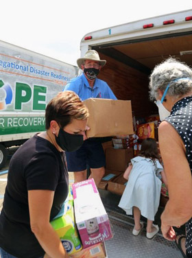 Louisiana Conference Bishop Cynthia Fierro Harvey (at left) and Texas Conference Bishop Scott Jones (center) help unload supplies at Broadmoor United Methodist Church in Baton Rouge, La. The Texas Conference brought two trucks full of nonperishable foods and other targeted supplies to a staging area at the church. Photo courtesy of the Texas Conference.