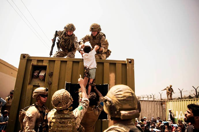 UK and Turkish coalition forces and U.S. Marines assist a child during an evacuation at Hamid Karzai International Airport in Kabul, Afghanistan, on Aug. 20. While the last U.S. forces have left the country, United Methodists are still working with ecumenical partners there to improve conditions for people in Afghanistan. Photo by U.S. Marine Corps Staff Sgt. Victor Mancilla, courtesy of the U.S. Department of Defense.