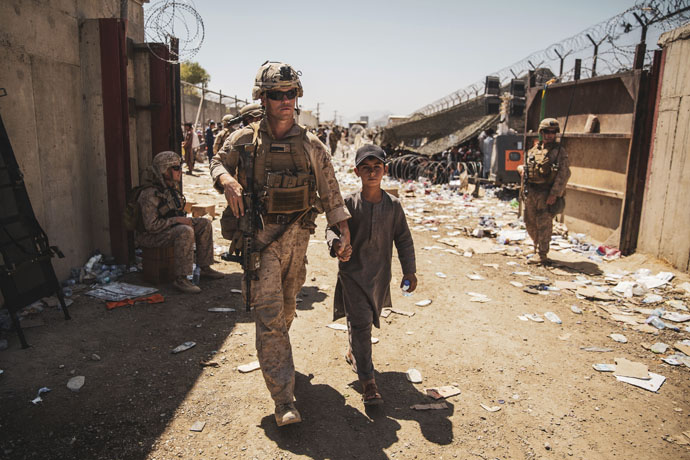 A U.S. Marine with the Special Purpose Marine Air-Ground Task Force-Crisis Response-Central Command escorts a youth to his family during an evacuation at Hamid Karzai International Airport in Kabul, Afghanistan, on Aug. 24. Photo by U.S. Marine Corps Staff Sgt. Victor Mancilla, courtesy of the U.S. Department of Defense.