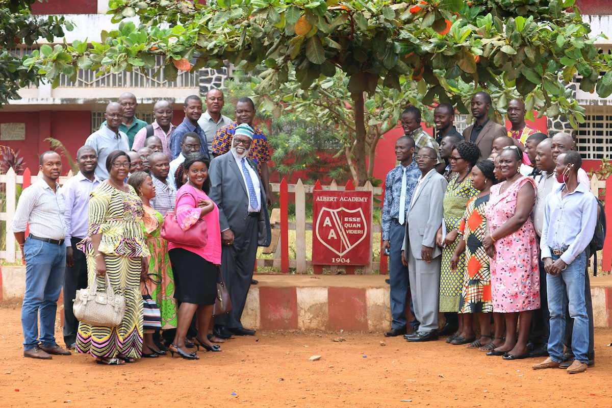 United Methodist Bishop Warner Brown (to the left of sign, middle row) poses with staff of the Albert Academy boys' high school in Freetown, Sierra Leone, during a familiarization tour of United Methodist institutions in the country. Brown was appointed as interim bishop of the Sierra Leone Episcopal Area following the death of Bishop John K. Yambasu in 2020. Photo by Phileas Jusu, UM News.