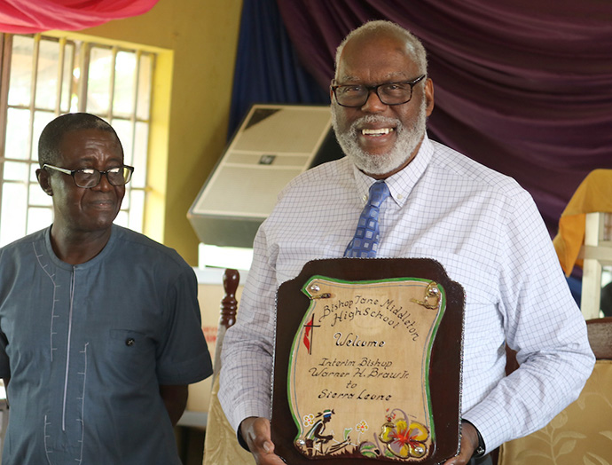Bishop Warner Brown holds a plaque given to him by staff of the Bishop Jane Middleton High School in Freetown when he toured the facility. Photo by Phileas Jusu, UM News.