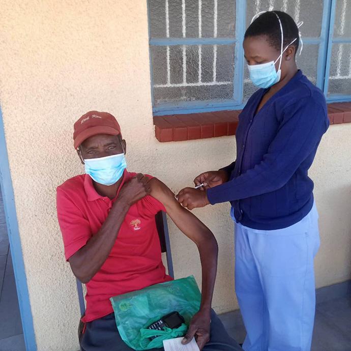 Pharaoh Mukototsi receives a COVID-19 vaccination from nurse Belinda Mashoko at The United Methodist Church's Dindi Clinic in Zimbabwe. Photo by Kudzai Chingwe, UM News.