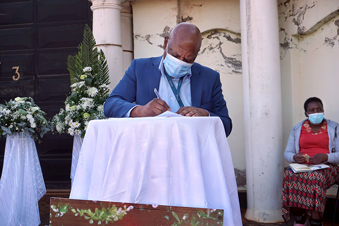 Micheal Dengwani writes a message of condolence during the outdoor funeral of Lillian Chikomo in Harare, Zimbabwe. Photo by Kudzai Chingwe, UM News.