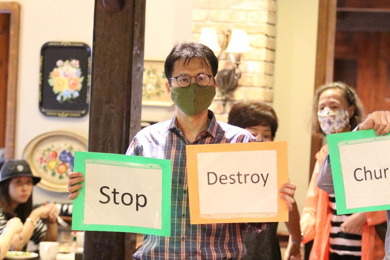 아틀란타한인교회의 한 교인이 김세환 목사의 기자회견장 앞에서 교회를 탄압하지 말라는 구호를 쓴 팻말을 들고 서 있다. 이 자리에는 약 50여 명의 교인이 함께했다. 사진, 김응선, 연합감리교회.