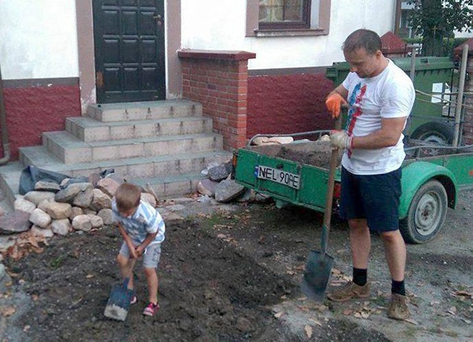 The Rev. Dariusz Zuber gets a little help from his son, Staś, while working in the churchyard at God's Love United Methodist Church in Ełk, Poland. Photo courtesy of the Rev. Dariusz Zuber.