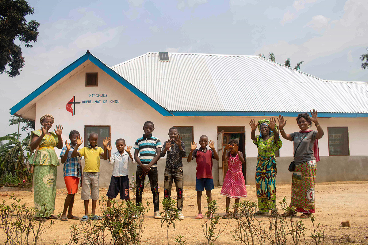Children and staff wave from in front of the new United Methodist orphanage in Kindu, Congo. The facility, constructed from sustainable materials, was built with funding from the United Methodist Board of Global Ministries. Photo by Chadrack Tambwe Londe, UM News.