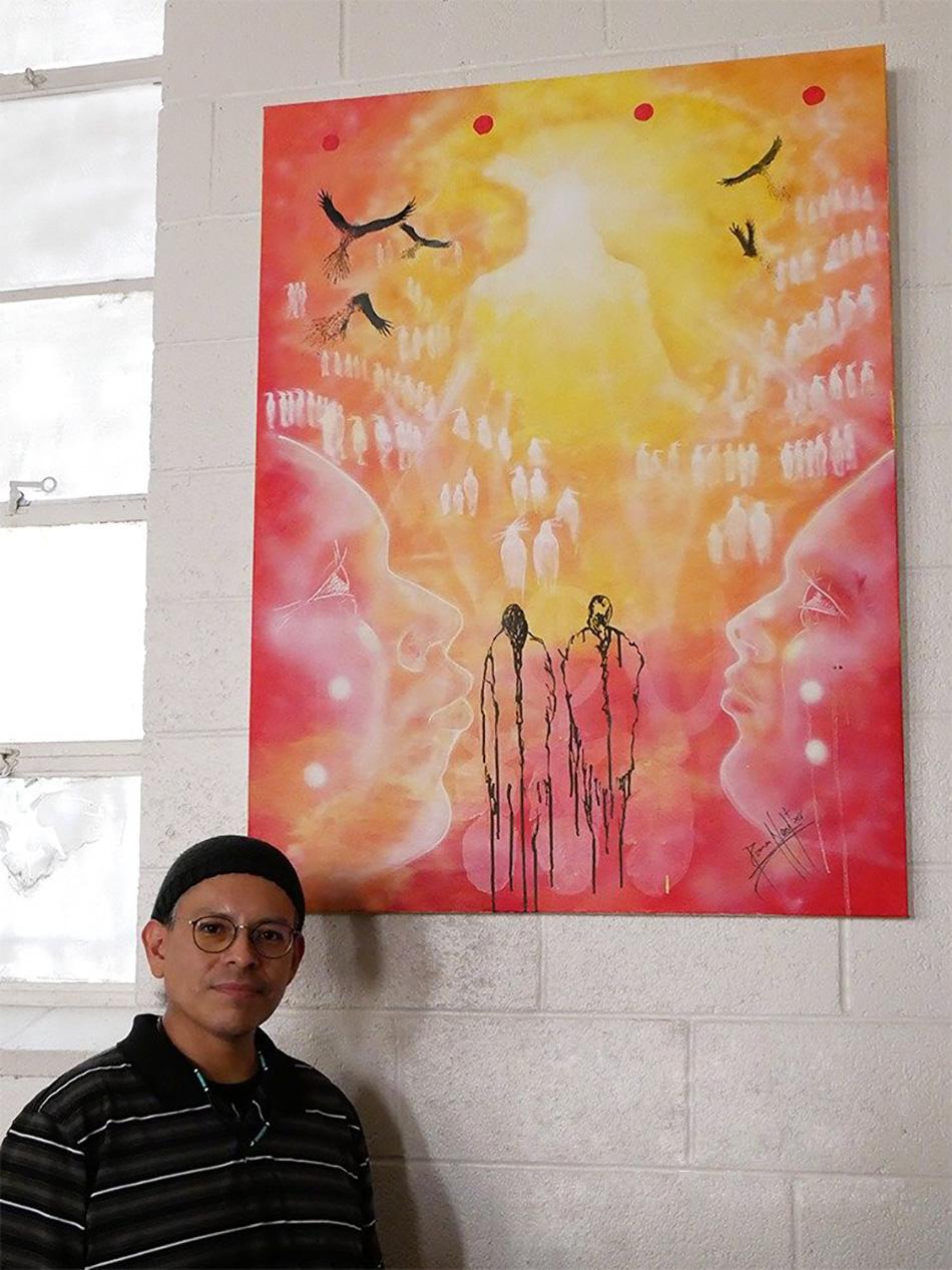 El artista Damon Neal posa junto a otra de sus obras que se exhiben en la IMU Indígena de Dallas, estado de Tejas. Foto cortesía de la Conferencia Anual del Norte de Tejas.