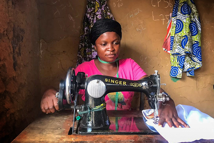 Henriette Kibibi, 22, sews uniforms in her workshop near Kindu, Congo. Kibibi, a mother of two, received vocational training at the Mama Lynn Center in Kindu that helps her support her family. Photo by Chadrack Tambwe Londe, UM News.