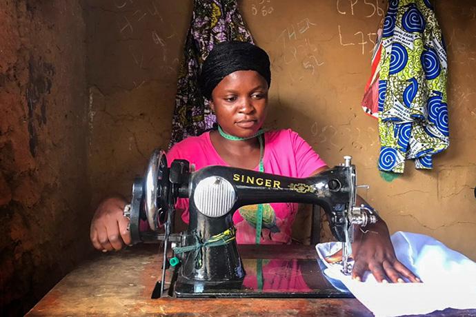 Henriette Kibibi, 22 ans, coud des uniformes dans son atelier situé dans un Quartier périphérique de Kindu, au Congo. Kibibi, mère de deux enfants, a reçu une formation professionnelle au Centre Mama Lynn de Kindu qui l'aide à subvenir aux besoins de sa famille. Photo de Chadrack Tambwe Londe, UM News.