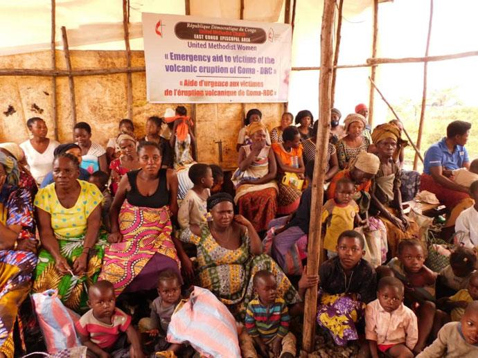 Des femmes veuves attendent la distribution de la nourriture au camp des déplacés de Bojuvu 1 dans le territoire de Nyirango au Sud Kivu. De nombreuses femmes et des veuves souffrent pendant cette période après que leurs champs aient été calcinés par le feu du volcan. L'Eglise a apporté une assistance aux femmes veuves et orphelins. Photo par Jolie Mulebinge, UM News.